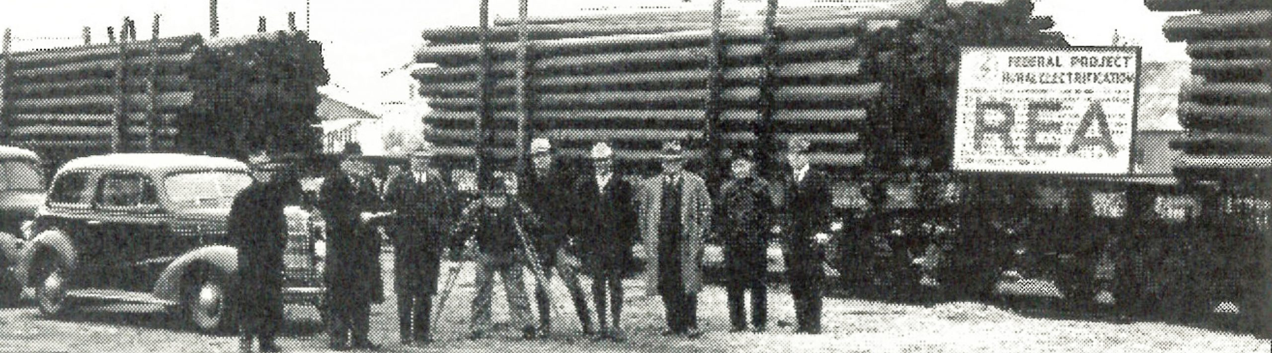 Old photo from the history of OEC. Workers in front of electrical poles
