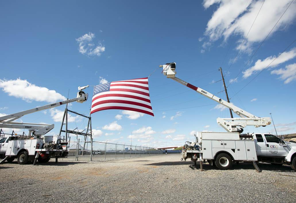 OEC work trucks holding up the US flag